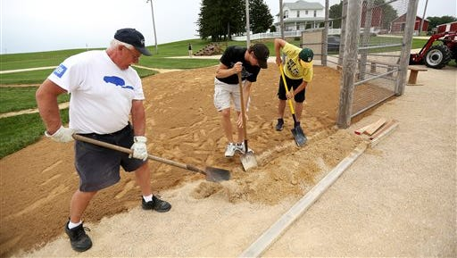 Volunteers Al Steffen left, Sam Deutmeyer, center, and Ben Loeffelholz work on the infield of the Field of Dreams in Dyersville, Iowa, in preparation for this weekend's festivities held.