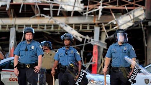 Police wearing riot gear stage outside the remains of a burned convenience store Monday in Ferguson, Mo. The FBI opened an investigation Monday into the death of 18-year-old Michael Brown, who police said was shot multiple times Saturday after being confronted by an officer in Ferguson. Authorities in Ferguson used tear gas and rubber bullets to try to disperse a large crowd Monday night that had gathered at the site of a burned-out convenience store damaged a night earlier, when many businesses in the area were looted.