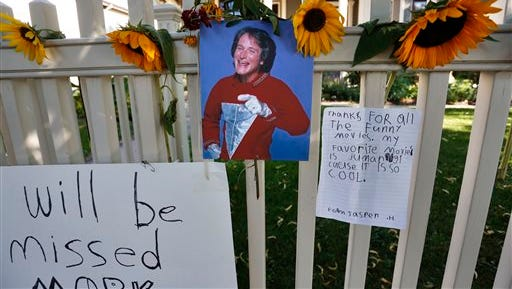 A photo of the late actor Robin Williams playing Mork from Ork hangs with flowers and notes left by people paying their respects, at a makeshift  memorial in Boulder, Colo., Tuesday Aug. 12, 2014, outside the home where the 80s TV series Mork & Mindy, starring Williams, was set. Williams, the Academy Award winner and comic supernova whose explosions of pop culture riffs and impressions dazzled audiences for decades and made him a gleamy-eyed laureate for the Information Age, died Monday, Aug. 11, in an apparent suicide. He was 63.
