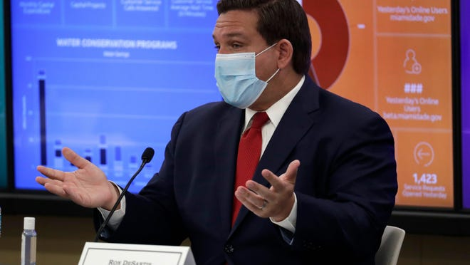 Gov. Ron DeSantis gestures during an appearance with Miami-Dade County mayors on Tuesday. At least he's wearing a mask.