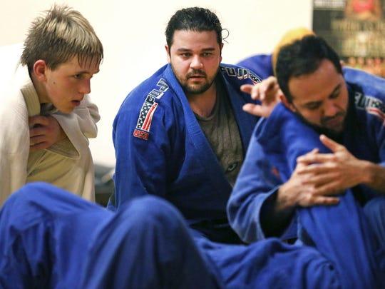 Rameen Almozaffar, center, and Ethan Welch, left, watch Rameen's brother, Sensei Hamid Reza Almozaffar demonstrate a hold Tuesday, Nov. 14, 2017, in Appleton, Wis. Rameen Almozaffar qualified for the U.S. team in judo.