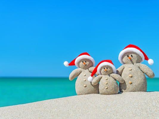 Family of Christmas Snowmen in santa hats at tropical beach.