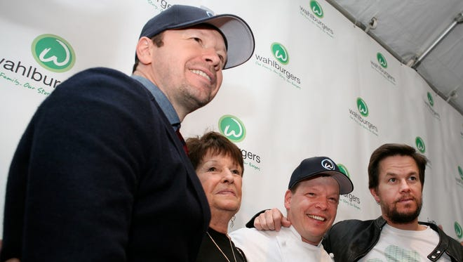 Donnie, Paul and Mark Wahlberg with their mom at a grand opening of the  the burger chain's location in Hingham, Mass.