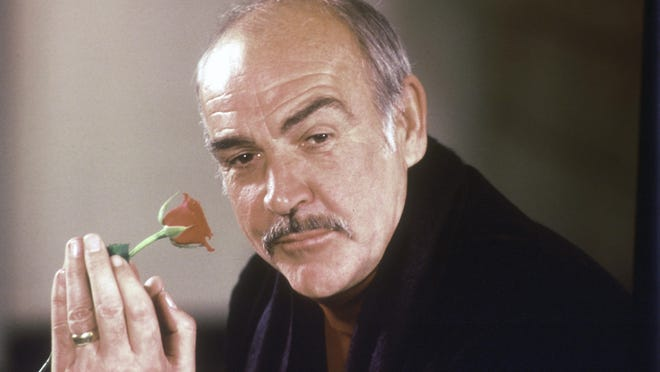 """Actor Sean Connery holds a rose in his hand as he talks about his new movie """"The Name of the Rose"""" at a news conference in London, England, Jan. 23, 1987."""