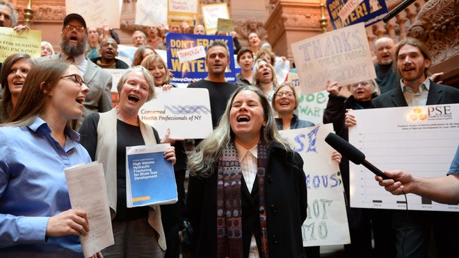 "Singer Natalie Merchant leads a group of anti-fracking activists in singing ""This Land is Our Land"" at the New York State Capitol building in Albany in December. They were thanking Gov. Andrew Cuomo and Department of Environmental Conservation officials for banning high-volume hydraulic fracturing."