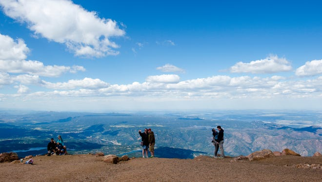 Visitors takes photos at the top of Pikes Peak Tuesday, Aug. 4, 2015, near Colorado Springs, CO.