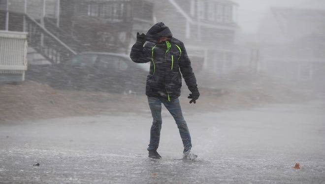 A pedestrian makes his way long Turner Road in Scituate, Mass on March 13, 2018.
