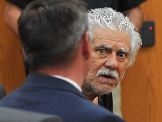 Wayne Burgarello, background, listens to his public