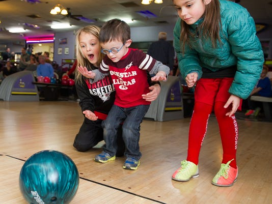 Sisters, Tyler Elliott, age 9, left and Dylan, right, age 8, share their brother's first try at bowling Sunday February 10, 2013 at Suburban Bowlerama in York Township. Garver Elliott, age 4, center, is legally blind and had been hesitant to try bowling before the Tony Petraco Memorial Bowl-a-thon, to benefit ForSight Vision.    YORK DAILY RECORD/SUNDAY NEWS - PAUL KUEHNEL