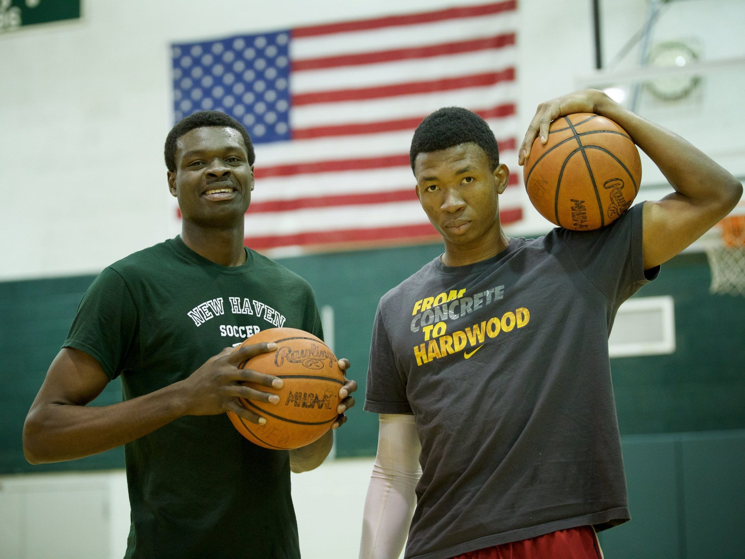 New Haven juniors Innocent Nwoko, left, and Jerry Ben pose during an open gym at the high school Wednesday. Both moved to the United States from Nigeria in 2013. After only two years of playing basketball, each has received a college scholarship offer.
