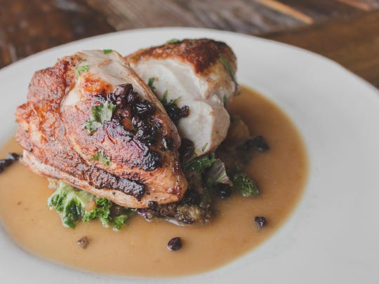 Mary's Organic Chicken breast at Roundabout Grill features de-boned and brined chicken, sausage bread pudding, braised spinach, and a finishing flourish of chicken demi-glace and port wine currants.
