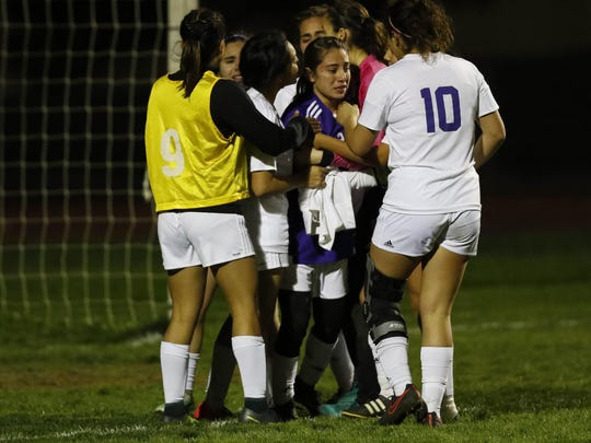 Soledad's Belinda Ascencio (center) is hugged by her teammates after losing to King's Academy during a girls CCS Division II playoff match at Soledad High School.