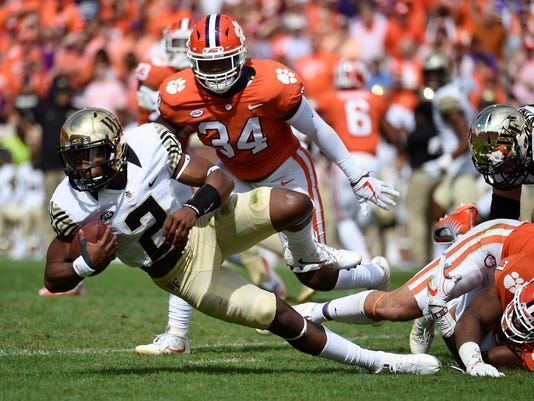 Wake Forest quarterback Kendall Hinton (2) is tackled by Clemson defensive end Austin Bryant (7) as Clemson linebacker Kendall Joseph (34) defends during the first half of an NCAA college football game, Saturday, Oct. 7, 2017, in Clemson, S.C. (AP Photo/Rainier Ehrhardt)