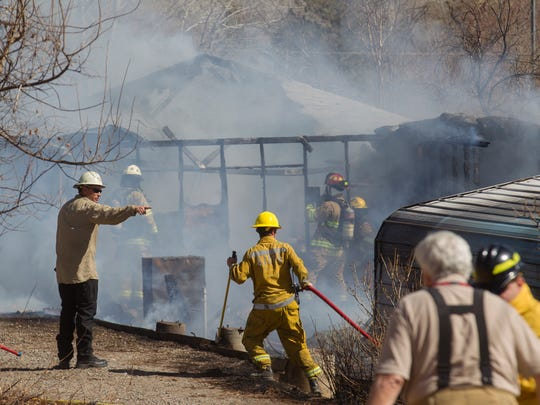 At left, San Juan County Fire Chief Craig Daugherty works with his crew to contain a structure fire on Wednesday, March 14, 2018 at 50 County Road 3535 in Flora Vista.