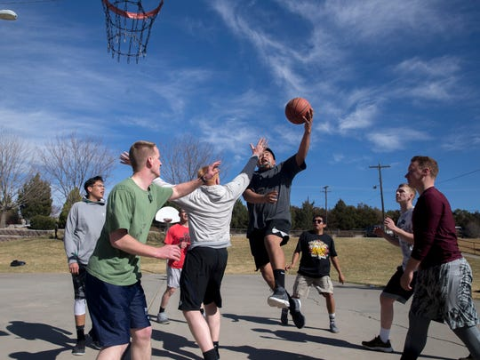 Missionaries from the Church of Jesus Christ of Latter-Day Saints play basketball on Monday at the basketball courts at Brookside Park in Farmington.