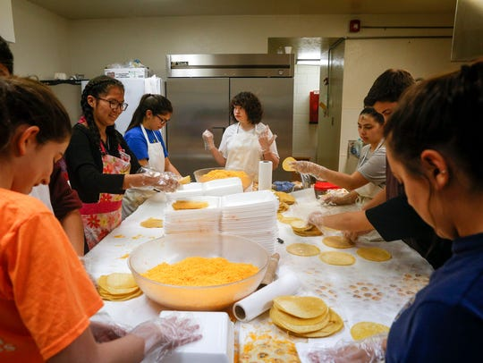 St. Mary's Youth Group members assemble enchiladas on Feb. 13, 2018, during the annual Cheese Enchilada Take-Out sale at St. Mary's Parish Center in Farmington.
