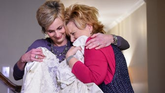 Shannon McNamara, left  and Kim Jones hug each other as they exchange their wedding dresses Monday Jan. 23, 2017, in Franklin, Tenn. The two women got sent home with each other's wedding dresses 30 years ago and only recently discovered the mix-up.