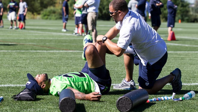 Seattle Seahawks safety Earl Thomas, left, gets help stretching from a team staff member during NFL football training camp on Friday, July 31, 2015, in Renton, Wash.