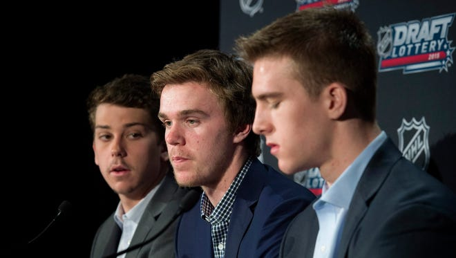 Connor McDavid, center, speaks to reporters with fellow potential draftees Dylan Strome, left, and Noah Hanifin following the announcement of the NHL Draft Lottery in Toronto on Saturday, April 18, 2015.