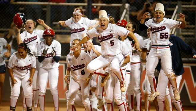Arizona celebrates after Chelsea Goodacre ties the game in the bottom of the seventh inning with a two-run home run against Minnesota during an NCAA college softball tournament regional championship game, Sunday, May 17, 2015, in Tucson, Ariz.