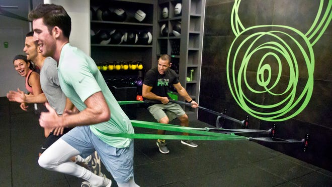 "Gym instructor Javier ""Coach Java"" Martinez, far right, trains clients how to run using resistant bands at the Fhitting Room boutique fitness studio, Tuesday, June 23, 2015, in New York."