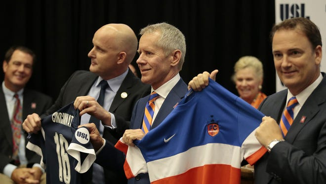 United Soccer League president Jake Edwards (left) presents new owner and CEO Carl Lindner III (center) and and general manager Jeff Berding (right) with the USL franchise and jerseys at a press conference to introduce the new FC Cincinnati professional soccer team at the University of Cincinnati in Cincinnati.