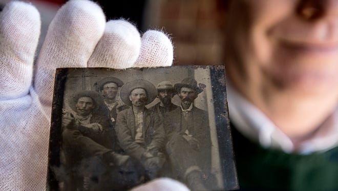 Lawyer Frank Abrams of Asheville, N.C., holds up a tintype picture Jan. 5, 2016, of five men in hats with cigars and whiskey, one of them believed to be Billy the Kid. If so, the $10 flea-market find could be worth millions.