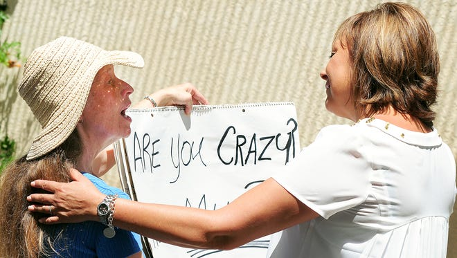 Melody Burns of Las Cruces, left, and Gov. Susana Martinez discuss the sign Burns created in July 2013 opposing the state's decision to abruptly suspend Medicaid funding to Southwest Counseling Center and other providers within the state.