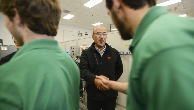 ARJ President Kimihiko Sumino shakes hands with students in the advanced maintenance technician program at Jackson State Community College in this February 2015 file photo. ARJ Manufacturing LLC donated the robotic weld cell to the Jackson State industrial technology lab to help teach students robotic maintenance and programming.