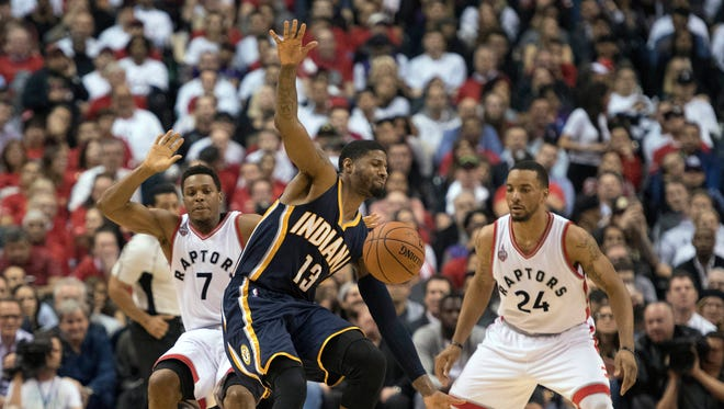 Pacers forward Paul George (13) battles for a ball with Toronto Raptors guard Norman Powell (24) and guard Kyle Lowry (7) during the fourth quarter in game five of the first round of the 2016 NBA Playoffs at Air Canada Centre. The Toronto Raptors won 102-99.