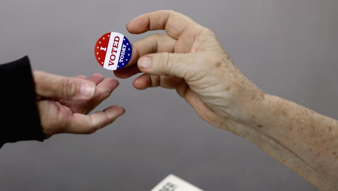 Voters get an 'I VOTED TODAY' sticker after casting their ballots at the Red Oak (Iowa) Fire Department on Nov. 4, 2014.