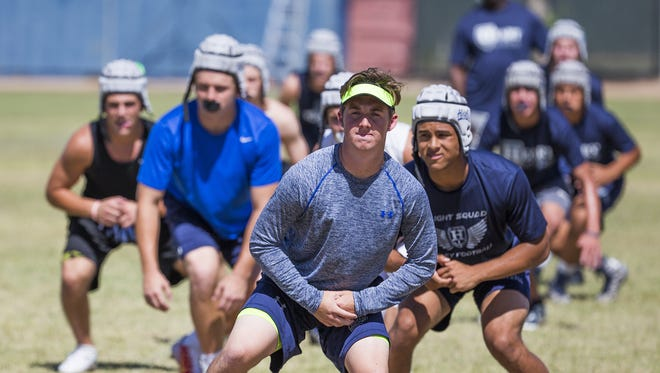 Higley High School quarterback Mason Crossland, visor, in front and center during stretching before practice at the school, Wednesday, May 11, 2016.