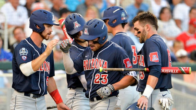 Arizona's Zach Gibbons (23) is congratulated by Louis Boyd, left, JJ Matijevic, second from left, and Cody Ramer, right, on his two-run hit in the fifth inning of an NCAA men's College World Series baseball game against Miami in Omaha, Neb., Saturday, June 18, 2016.