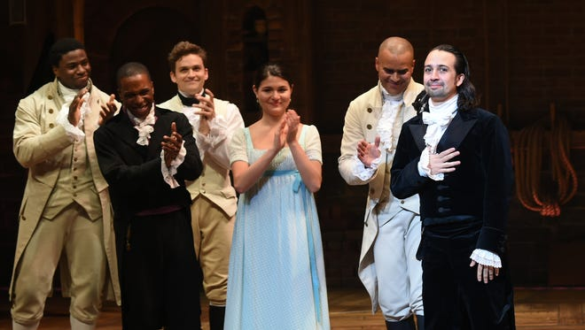 """Actors Leslie Odom Jr., left, Phillipa Soo, and Christopher Jackson look on as actor and """"Hamilton"""" creator Lin-Manuel Miranda, right, takes his final performance curtain call at the Richard Rogers Theatre after a performance of """"Hamilton"""" on Saturday, July 9, 2016, in New York."""