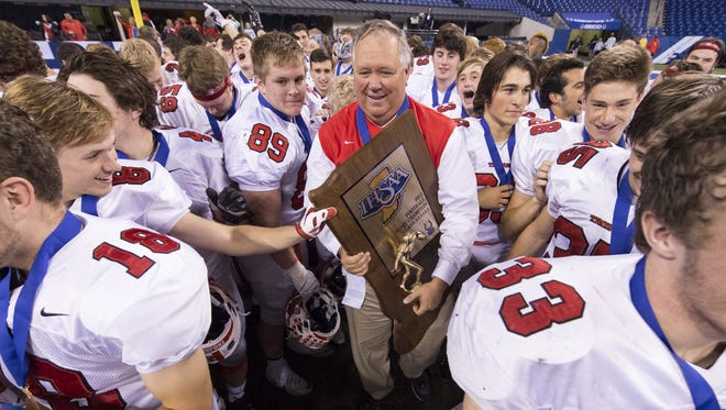 Center Grove coach Eric Moore celebrates with his team after winning the IHSAA Class 6A State Championship game, Nov. 28, 2015, at Lucas Oil Stadium.