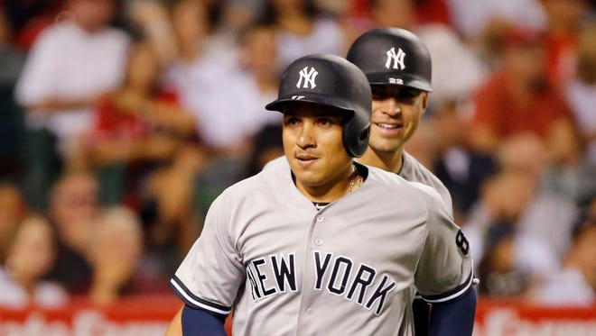 The New York Yankees' Ronald Torreyes heads for the dugout after being congratulated on his home run by Jacoby Ellsbury, rear, during the fifth against the Los Angeles Angels in a baseball game in Anaheim, Calif., Friday, Aug. 19, 2016.
