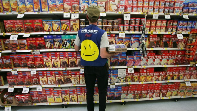 An employee restocks a shelf in the grocery section of a Wal-Mart Supercenter in Troy, Ohio.