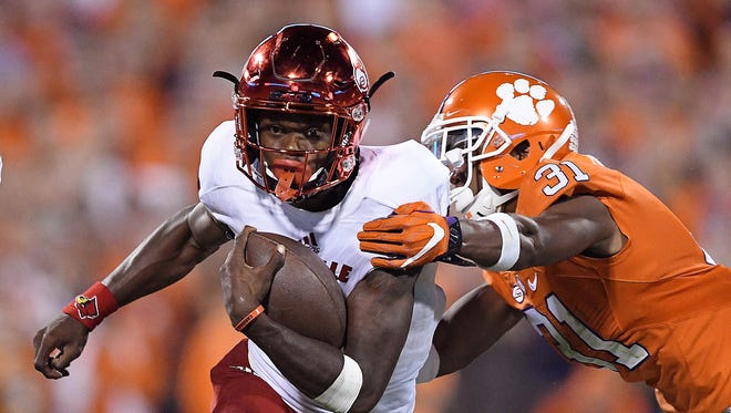 CLEMSON, SC - OCTOBER 01: Lamar Jackson #8 of the Louisville Cardinals looks to avoid the tackle of Ryan Carter #31 of the Clemson Tigers during the fourth quarter at Memorial Stadium on October 1, 2016 in Clemson, South Carolina.  (Photo by Grant Halverson/Getty Images) ORG XMIT: 659650717 ORIG FILE ID: 611919510