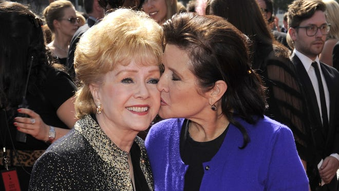 Carrie Fisher kisses her mother, Debbie Reynolds, as they arrive at the Emmy Awards in 2011.