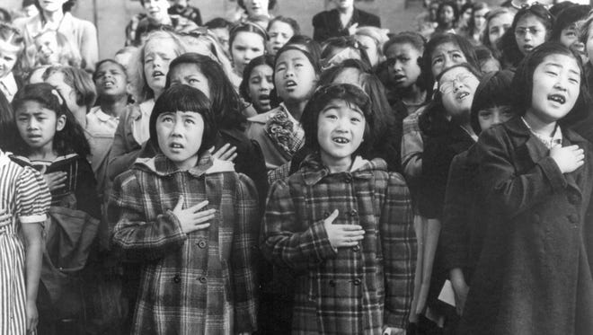 In this April 1942 photo made available by the Library of Congress, children at the Weill public school in San Francisco recite the Pledge of Allegiance. Some of them are evacuees of Japanese ancestry who will be housed in War Relocation Authority centers for the duration of the war. Roughly 120,000 Japanese immigrants and Japanese-Americans were sent to camps that dotted the West because the government claimed they might plot against the U.S.