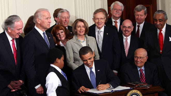 President Barack Obama signs the Affordable Care Act during a ceremony with fellow Democrats in the East Room of the White House on March 23, 2010 in Washington, D.C.