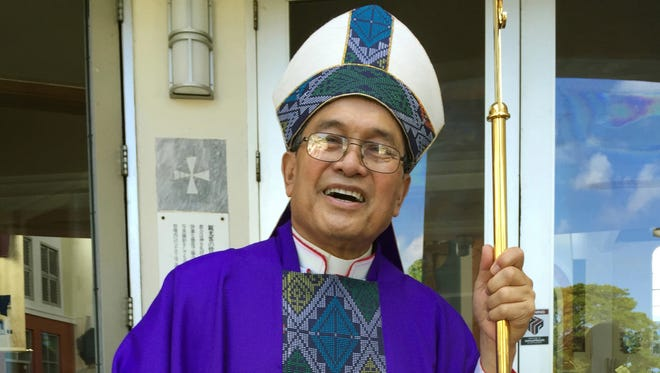 In this November, 2014 file photo, Archbishop Anthony Apuron stands in front of the Dulce Nombre de Maria Cathedral Basilica in Hagatna, Guam. T