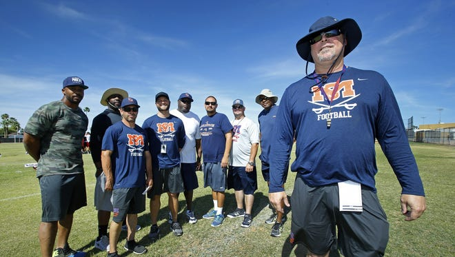 McClintock High head football coach Corbin Smith, right, has assembled a talented group of assistants Wednesday, April 26, 2017 in Tempe, Ariz. Smith is the son of the late college coach Larry Smith, who led programs at Arizona, Missouri, Tulane and USC.