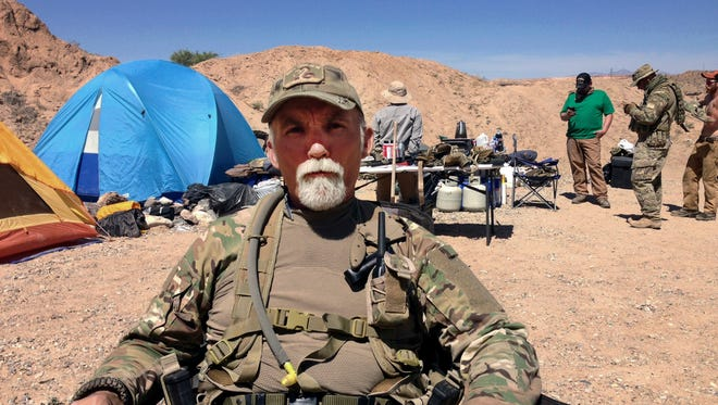 "In this April 16, 2014 file photo, Gerald ""Jerry"" DeLemus, of Rochester, N.H., sits with a group of self-described militia members camping on rancher Cliven Bundy's ranch near Bunkerville, Nev."