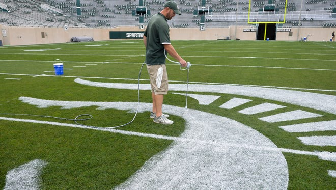 MSU Assistant Athletic Turf Manager Andy Flynn paints the Spartan logo on the 50 yard line Thursday, Aug. 31, 2017, at Spartan Stadium.  About 60-70 gallons of white paint is used to mark the field before each game.  [Matthew Dae Smith/Lansing State Journal]