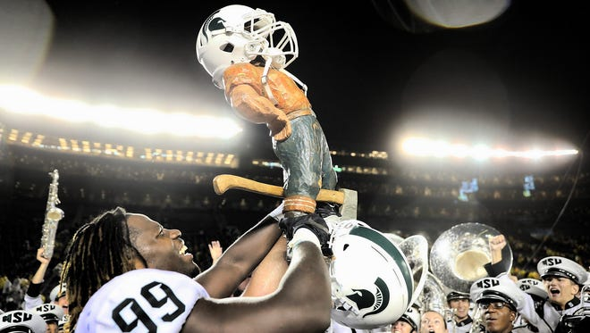Raequan Williams of the Michigan State Spartans celebrates a win against the Michigan Wolverines and carries the Paul Bunyan trophy after the game at Michigan Stadium.