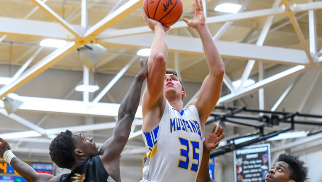 Madeira's Jack Cravaack (35) is fouled by Spartan defenders at Madeira High School, Friday, Dec. 1, 2017