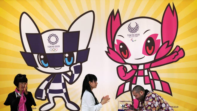 Ryo Taniguchi, right, the designer of the characters which will serve as mascots for the Tokyo 2020 Olympic Games and Paralympics Games, receives a 3D models of his designed characters.