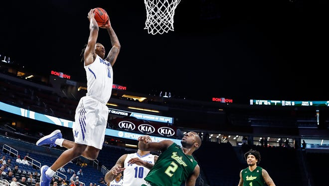 Memphis forward Kyvon Davenport (left) goes up for a dunk against the USF defense during second half action of their AAC first round tournament game in Orlando, Fl., Thursday, March 8, 2018.