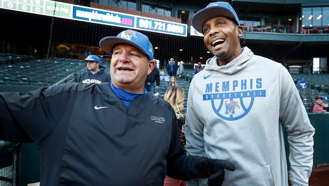 New University of Memphis head basketball coach Penny Hardaway (right) gets some advice from Tigers baseball manager Daron Schoenrock (left) before throwing out the first pitch at AutoZone Park Wednesday evening.